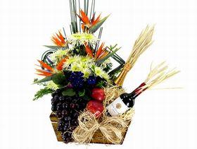 Arranjo com estrelízia, flores do campo, vinho Santa Helena Champagne Chandon, uvas e maças e vaso de violeta