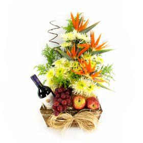 Arranjo com estrelízia, flores do campo, vinho Santa Helena, uvas e maças